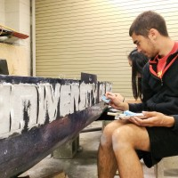 Jake paints canoe letters.