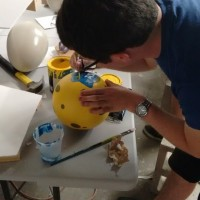 Noah paints the concrete bowling ball.