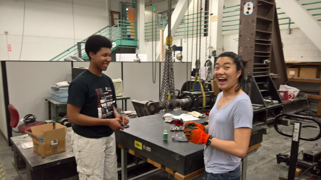 Steel bridge team members discuss how to manufacture a part.